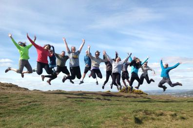 Students jumping for joy at the Seat of Arthur, Edinburgh, Scotland
